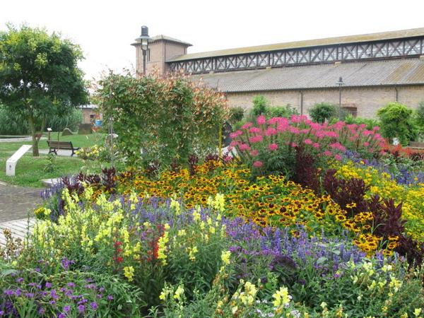 Maggio in fiore a Cervia: aiuole fiorite con, sullo sfondo, il Magazzino del sale.