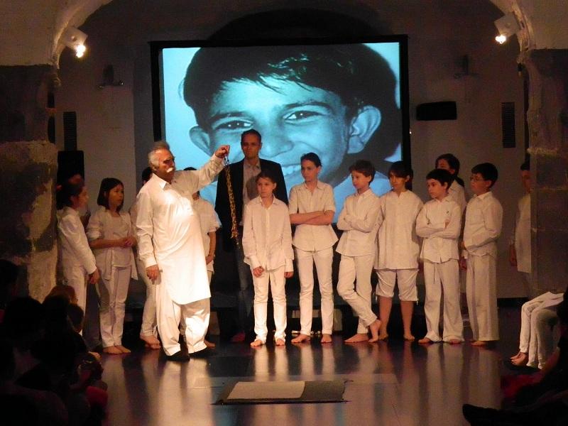 Genova, Palazzo Ducale. Alcuni dei ragazzi attori della compagnia teatrale di Enrica Origo con il sindacalista Ehsan Khan (terzo da sinistra) e, sullo sfondo, l'immagine di Iqbal Masih. (Foto di Giovanna Profumo)