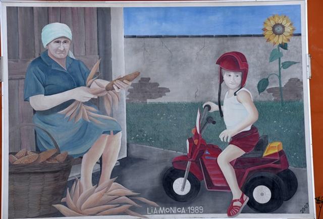 Generazioni e tradizioni antiche e nuove si incontrano nel piccolo paese. Il murale è firmato Lia-Monica 1989.