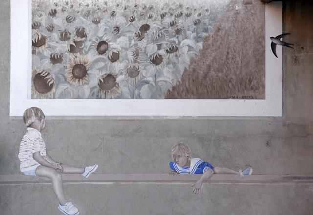 Luisa e Roberta eseguono questo murale. Due bambini su un muretto sembrano essere di fronte a una gigante cartolina con un campo di girasoli.