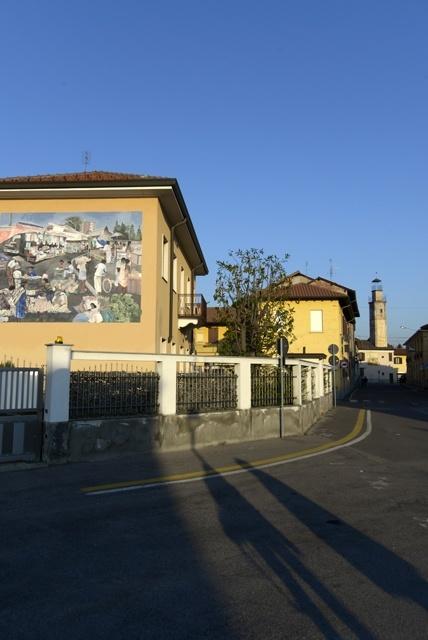 Scorcio di Dairago, si intravvede il murale 'Mercato globale' (1995) e le ombre dei giornalisti Salvatore Giannella e Benedetta Rutigliano.