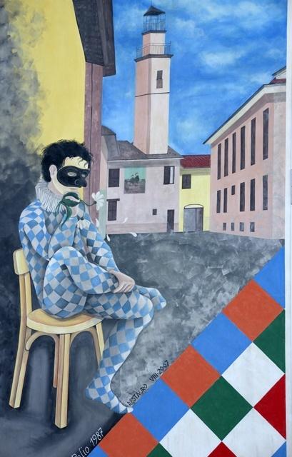 Uno scorcio di paese si apre dietro la maschera che veste i colori della contrada 'A Kruzeta'. Nell'angolo a destra i colori delle quattro contrade, altro omaggio al Palio (1987).