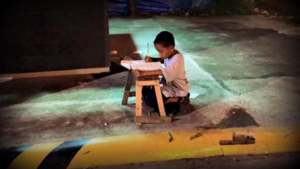 Bimbo-studia-in-strada-sotto-lampione