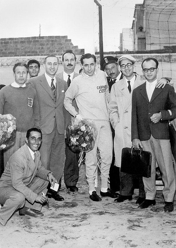 """Barletta 1959: Fausto Coppi posa prima della gara al velodromo """"Lello Simeone"""". Alla sua destra, il medico sportivo Ruggero Scommegna. Nella foto in apertura: Giro di Lombardia 1948, l'Airone ha preso il volo sulle rampe del leggendario Ghisallo."""