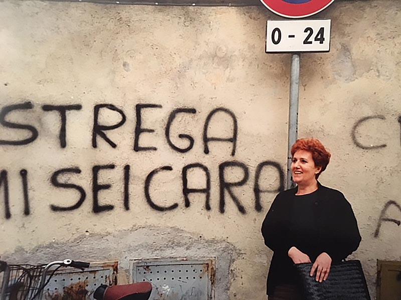 Silvana Giannini, la sposa da 59 anni di Gianni Giannini, davanti a una singolare scritta su un muro di Pennabilli