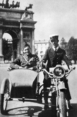 Hemingway nel 1918 nel carrozzino di un sidecar Indian Power Plus bicilindrico dell'esercito statunitense guidato da un amico davanti all'Arco della Pace di Milano