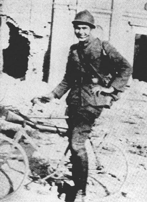 Ernest Hemingway in bicicletta e in divisa da bersagliere tra le rovine della chiesa di Fossalta