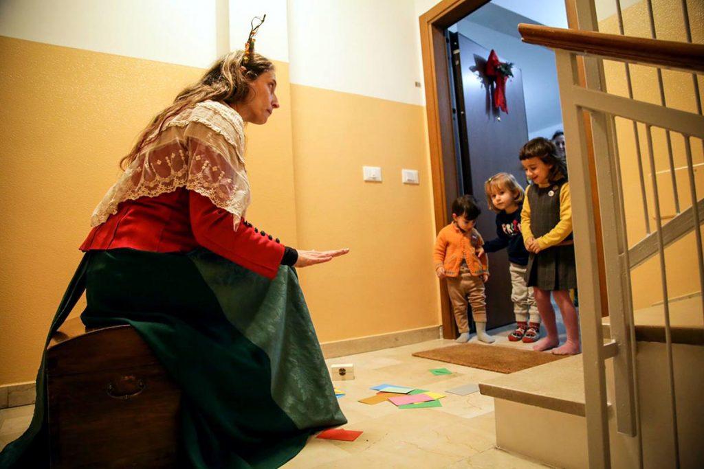 L'attrice Alessandra Amerio della compagnia modenese Peso Specifico Teatro, incanta dei bambini sulla soglia di una porta, durante una performance di Teatro Express