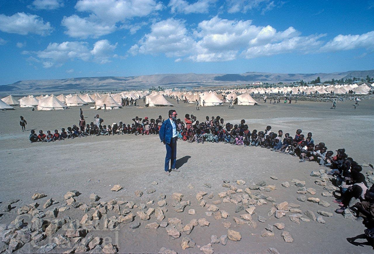 Macallè, Etiopia, 1985. Egidio Gavazzi con un gruppo di bambini nel campo della Cooperazione Italiana che assiste i rifugiati che qui affluiscono a causa della grande carestia