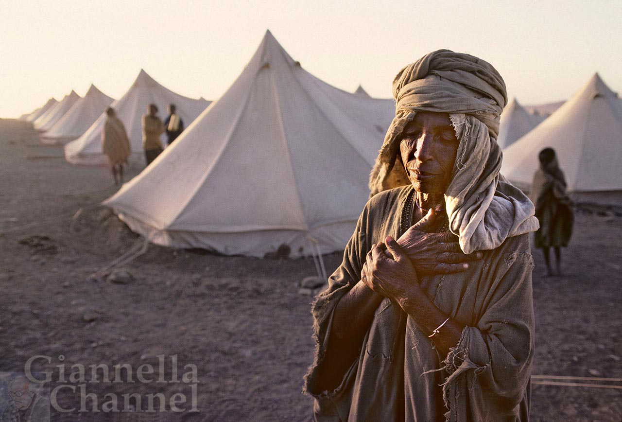 Macallè, Etiopia, 1985. Campo della Cooperazione Italiana per assistere i rifugiati della grande carestia. Donna in preghiera di ringraziamento